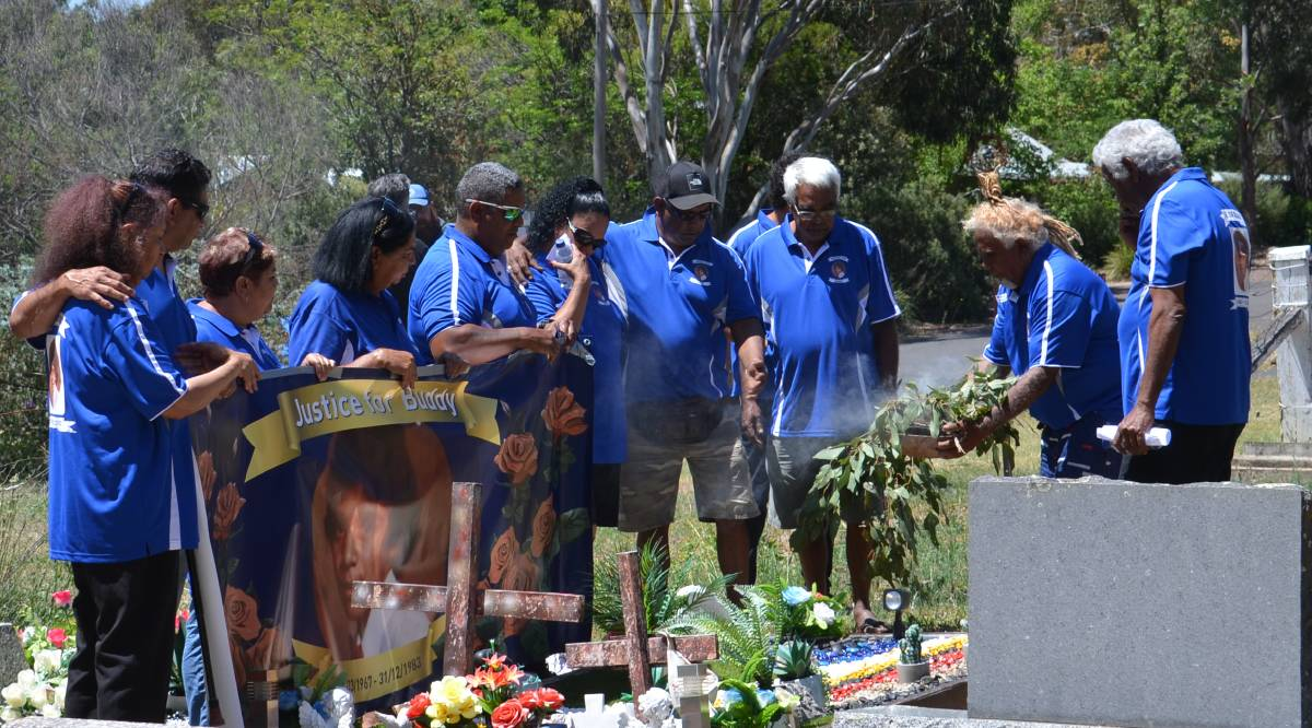 SPIRITUAL GUIDANCE: Lewis 'Buddy' Kelly's siblings gather around his grave during the smoking ceremony. Photo:Vanessa Arundale